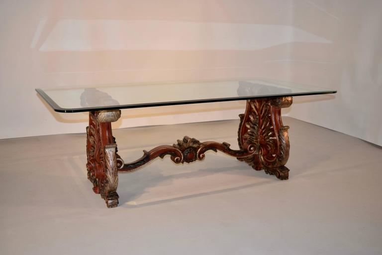 19th century hand-carved and painted wooden coffee table from Italy. The end supports are trestle shaped and are finely carved with acanthus leaves and pierced decoration over a carved scroll foot. The top is glass, and has a beveled edge and