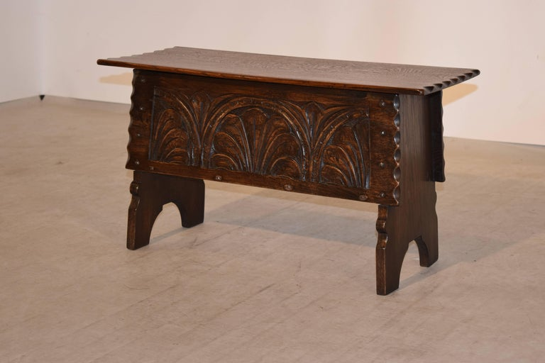 19th century oak bench with a lift top from England. The top is a single board with a pie crust edge, following down to a carved panel on the front, also with a pie crust edge. It has simple legs that are joined to the front and back with hand made