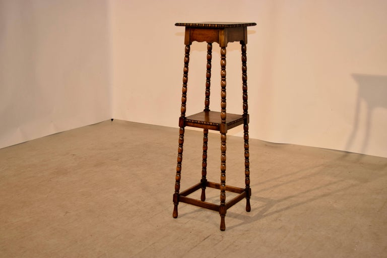 19th century English oak plant stand with a beaded edge around the top, following down to hand turned bob and stop legs. The legs are joined by a central shelf, also with a beaded edge and by simple stretchers at the bottom.