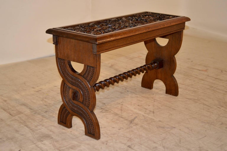 19th century English oak bench with detailed hand-carved top and pierced trestle legs, joined by a hand-turned barley twist stretcher.