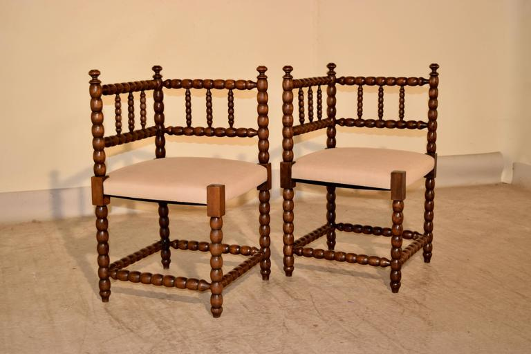 Pair of 19th-century French corner chairs made from oak. The frames are hand-turned in a spool design and the seats have been newly upholstered in linen.