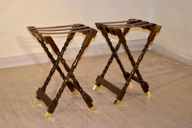 Pair of mahogany tray stands from England, circa 1920. The frames are hand-turned and have leather straps on the top and the feet are capped in brass. The stands open measure 21.25 W x 18.13 D x 30.25 H.