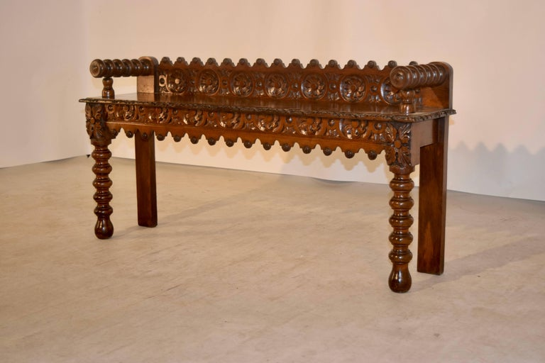 19th century English oak carved window seat with a lovely hand-carved and scalloped back, following down to hand turned arms, which are resting upon the seat, which has a hand carved and beveled edge over a gorgeous hand-carved and scalloped apron.
