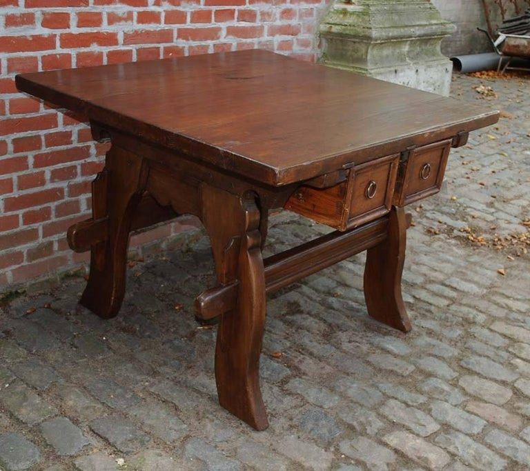 A beautiful bankers table or merchants table from switzerland. This table is made in solid walnut and has a nice and warm stained finish. The table has two drawers that slide both ways.  This is a typical banker table given its size and the sliding