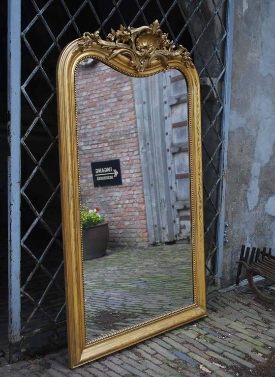 Extraordinary large antique French Louis Philippe mirror with a beautifully detailed cartouche. The mirror frame is largely gold leaf gilt and the gold color is very strong and intact after all these years. The gold leaf is partially polished to