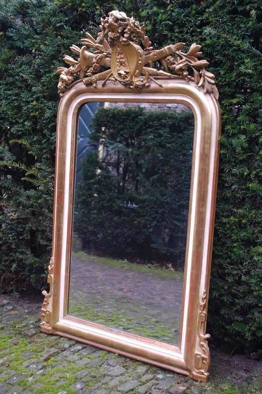 Exquisite 19th century French Louis Philippe mirror with detailed crest. The crest depicts musical instruments such as tambourine and flute that are surrounded by leaves and flowers. At the bottom corners, there are also two ornaments located. The