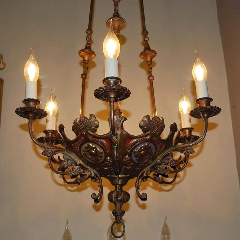 Pair of 19th century brass chandeliers. Each chandelier has six lights and new electric wiring. Beautiful colored details on the lower part of the chandelier.