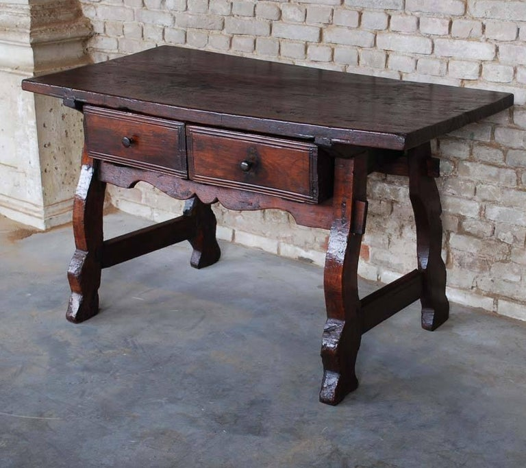 This beautiful rustic desk desk or sidetable was made in Northern Spain somewhere around 1760. The top is made from one solid plank of chestnut and is 1,18 inch thick. It is joined to the base with the typical dovetail connection. The table base has
