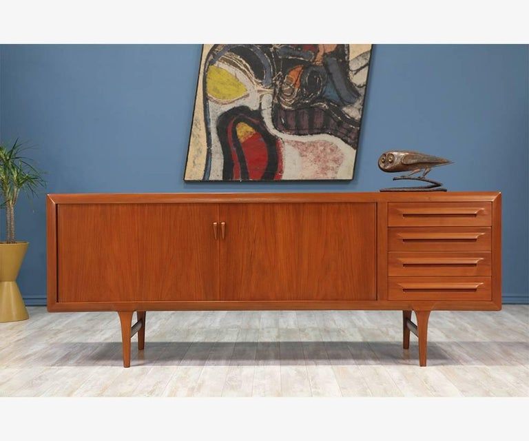 Tambour door credenza designed by Ib-Kofod Larsen for Faarup Møbelfabrik in Denmark circa 1950's. Impeccably crafted in teak wood, this beautiful credenza shows an intricate wood grain throughout and features smoothly functioning tambour doors that