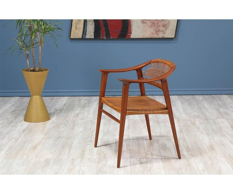 Classic Bambi armchair designed by Rolf Rastad and Adolf Relling for Gustav Bahus in Norway circa 1950's. Crafted with sculpted teak, this beautiful design features tapered legs and shows various shades of patina on the original woven cane seat