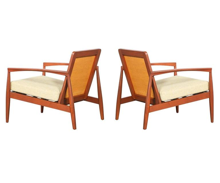 pair of danish modern teak lounge chairs with wicker back rest at