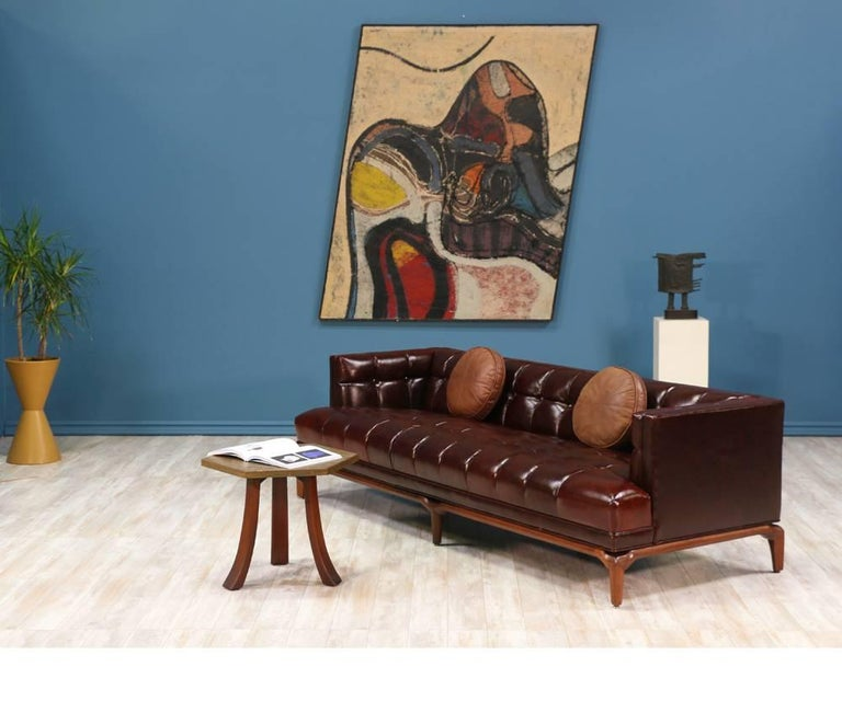 Fabulous biscuit tufted leather sofa designed by Maurice Bailey for Monteverdi-Young of Beverly Hills in the 1960's. This comfortable sofa is newly reupholstered in a full grain brown leather and set on a carved solid walnut wood base. Meticulously