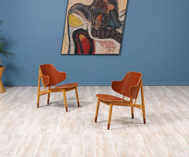 Pair of spectacular shell chairs, crafted by Danish architect and furniture designer Ib-Kofod Larsen, and manufactured by Christensen & Larsen A/S in the 1950's. Kofod Larsen's versatility to work with different types of wood, in this case creating