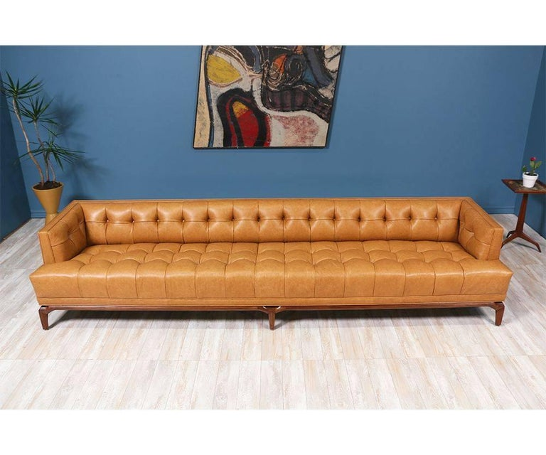 Spectacular biscuit tufted leather sofa designed by Maurice Bailey for Monteverdi-Young of Beverly Hills in the 1960's. This 10-foot comfortable sofa is newly reupholstered in a full grain leather and set on a carved solid walnut wood base. Designed