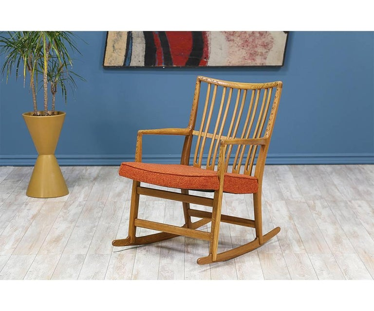 Rocking chair designed by Danish design pioneer, Hans J. Wegner, for Mikael Laursen in Denmark circa 1940. This Danish Modern iconic design is comprised of solid oak with a stunning floral ornamentation on the edges of the frame. Features an