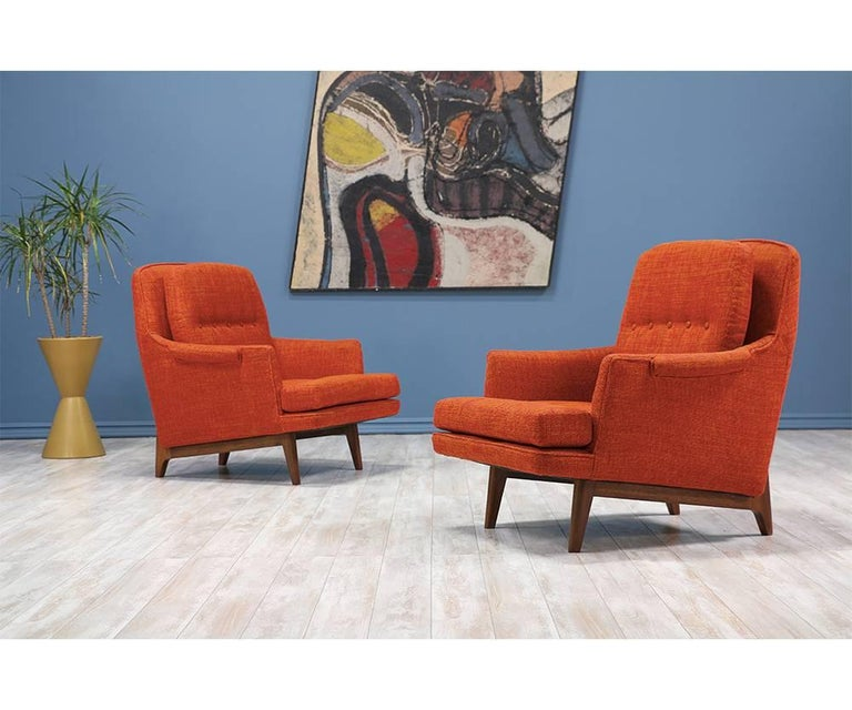 Pair of easy lounge chairs designed by Roger Sprunger for Dunbar in the United States circa 1960's. The model 484 features a solid walnut wood base that sits low to the ground with sculptured legs. Newly upholstered in a textured burnt orange tweed