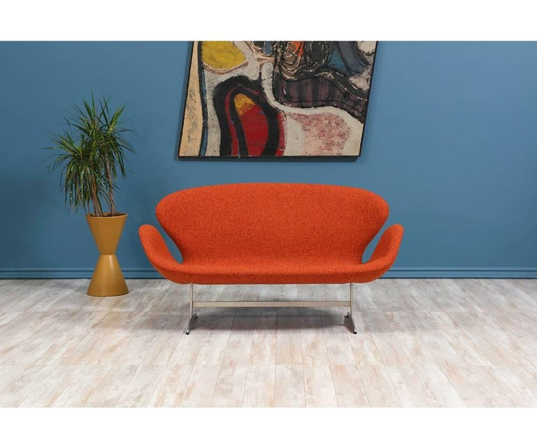 Originally designed for the SAS Royal Hotel in Copenhagen, the Swan sofa by Danish design pioneer, Arne Jacobsen, has become iconic and synonymous with Danish Modern. Reupholstered in a gorgeous orange tweed fabric, this comfortable design retains