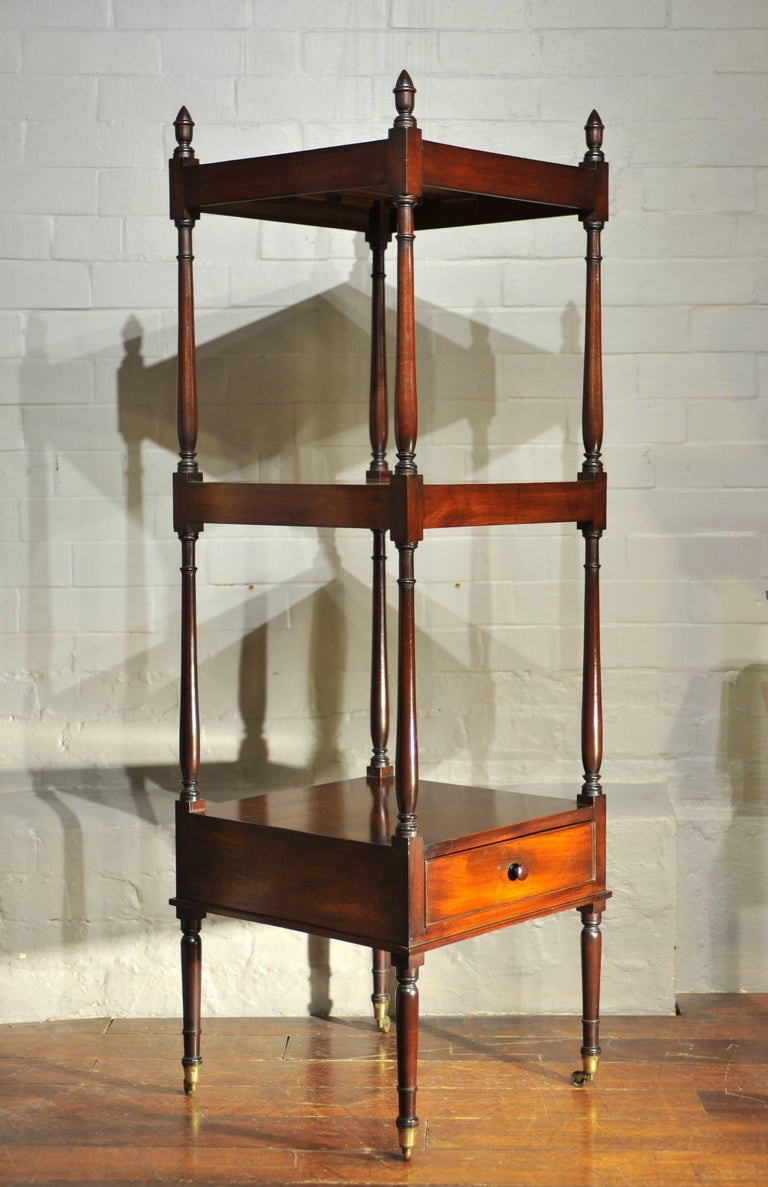 A fine and elegant Regency period mahogany whatnot. The slender turned and balluster shaped supports terminating with finials to the top and brass castors to the legs; the bottom tier with single drawer.