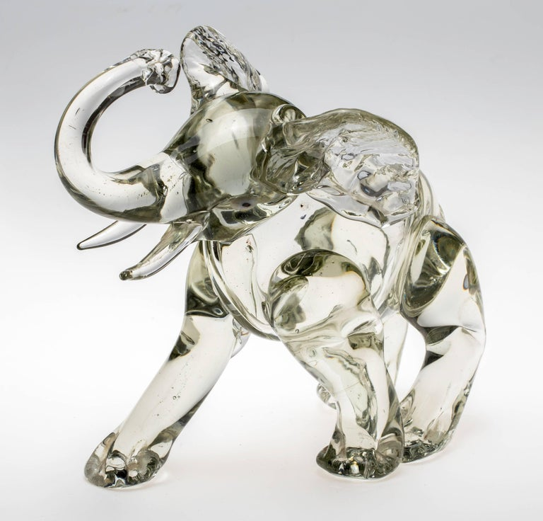 Beautifully made in Italy, Murano glass elephant sitting down on hind legs with its trunk up in the air. Chunky light grey color. Nice to touch.