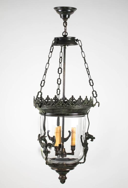Decorative three-light glass lantern is surrounded in cast bronze frame flanked with three griffins. Beautiful crown work finishes the top. Lantern itself is 15 x 20. Great for entry or hallway lighting.