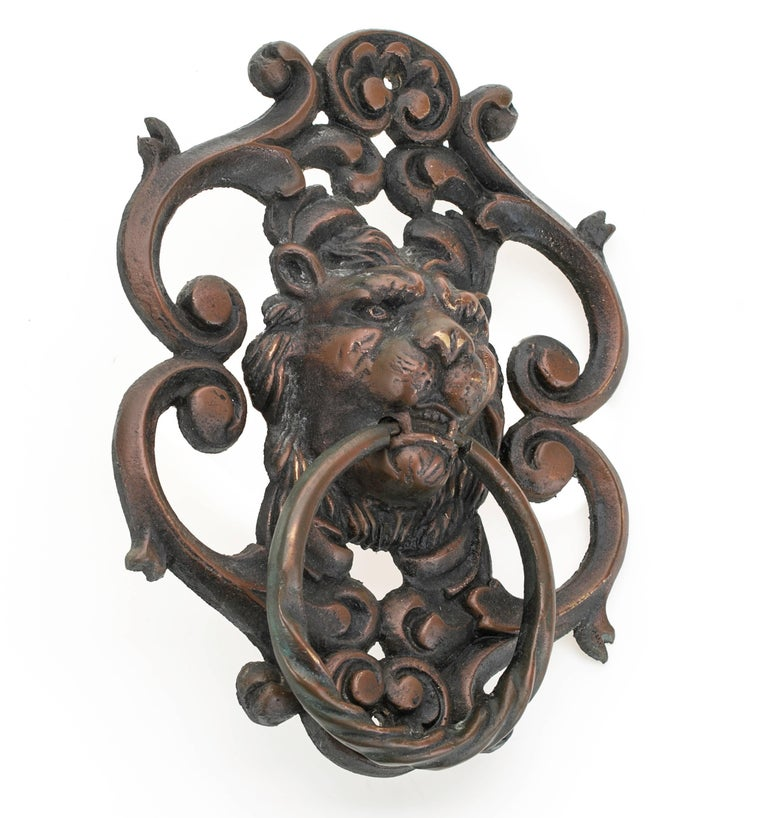 Cast bronze lion face door knocker, circa 1920s. Fierce looking lion head embellished in scrolled works, patinated bronze in copper finish. A very handsome stately piece.