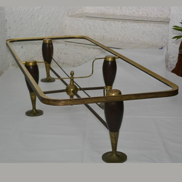For your consideration a vintage coffee table constructed with mahogany legs and bronze accents.