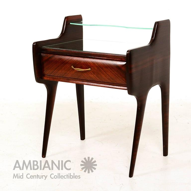 For your consideration a pair of bedside table constructed with rosewood and walnut veneer. Solid bras pull handles, floating glass top with mirror top. 