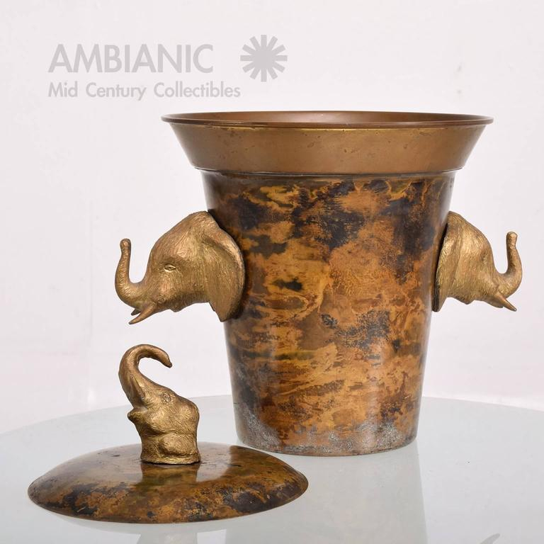 For your consideration a vintage ice bucket made of brass. Beautiful and unique. The bucket is made of brass and has a patinated églomisé finish on the brass. The handles are elephants made of solid brass. Matching lid.