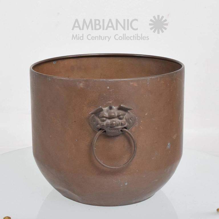 For your consideration a vintage bowl or planter in patinated brass.  Round shape with to side handles. The oval handles are attached to the planter by two dragon faces in brass.  Dings present and scuffs. Refer to images.  Unmarked. No