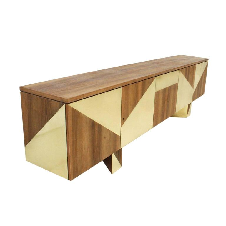 Handmade sideboard in solid walnut wood with brass veneer, composed of five bodies of doors and drawers.