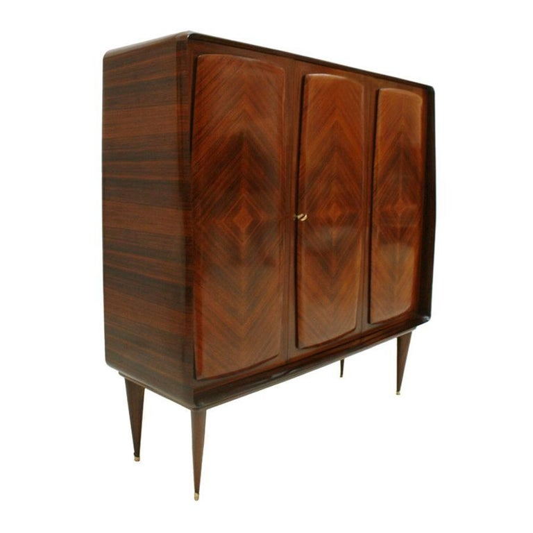 Three-door bar cabinet with drawers inside, made in solid wood clad in rosewood. Doors and marquetry made of rosewood. Legs with brass finish.