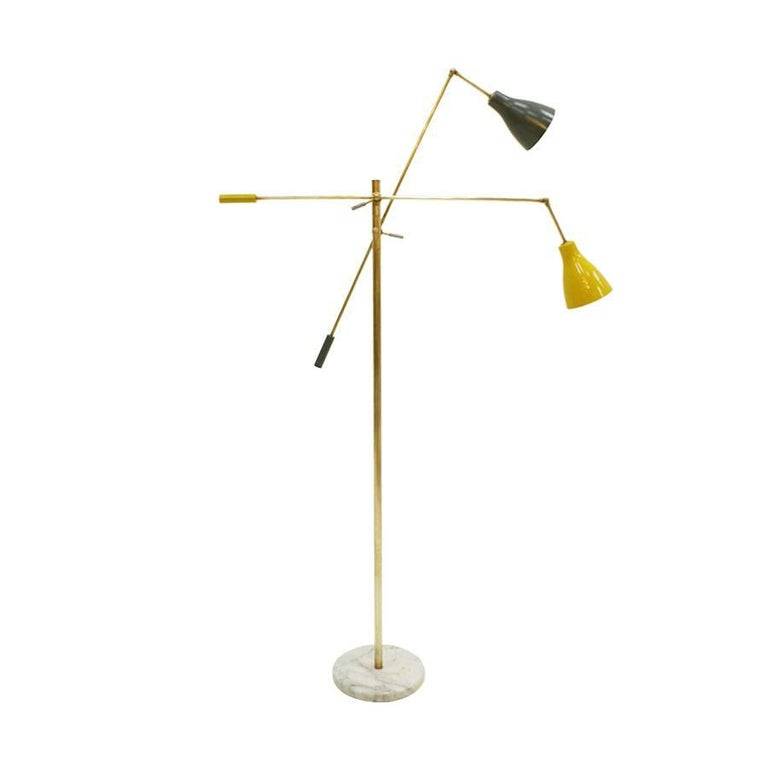 Floor lamp composed of two arms and adjustable cups with carrara marble base and brass structure.