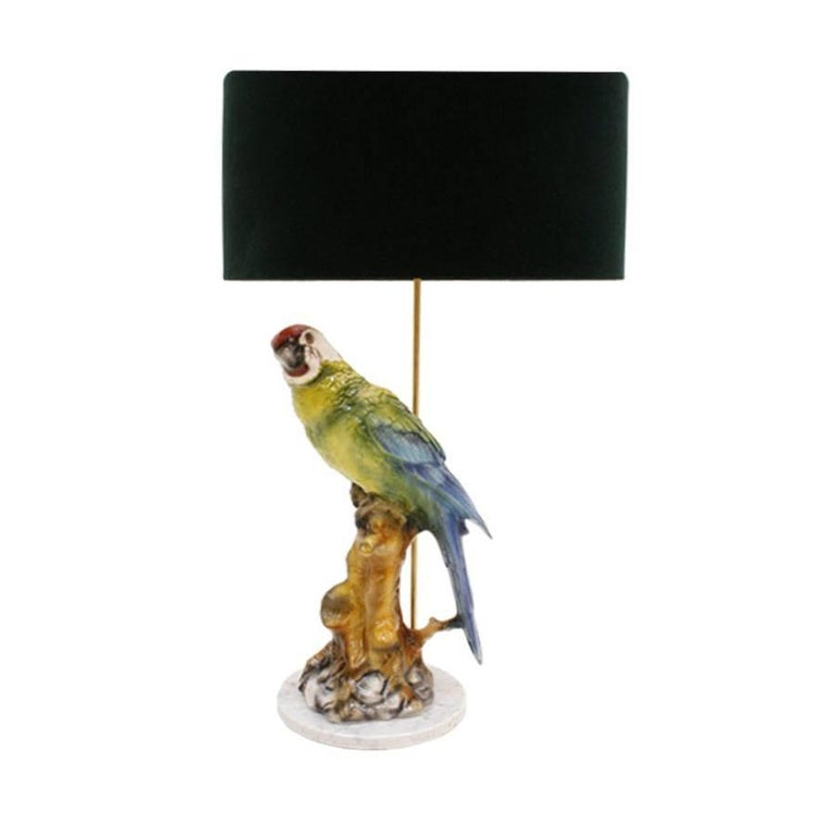 Pair of table lamps type Capodimonte, made with a circular white marble base, hand-painted porcelain macaw and brass stem. Lampshade made of green velvet and interior in golden chintz.