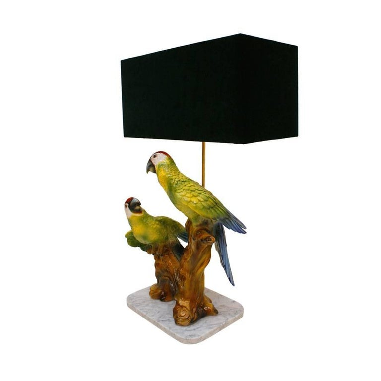 Table lamp type Capodimonte, made with a square white marble base, hand-painted porcelain macaw and brass stem. Lampshade made of green velvet and interior in golden chintz.