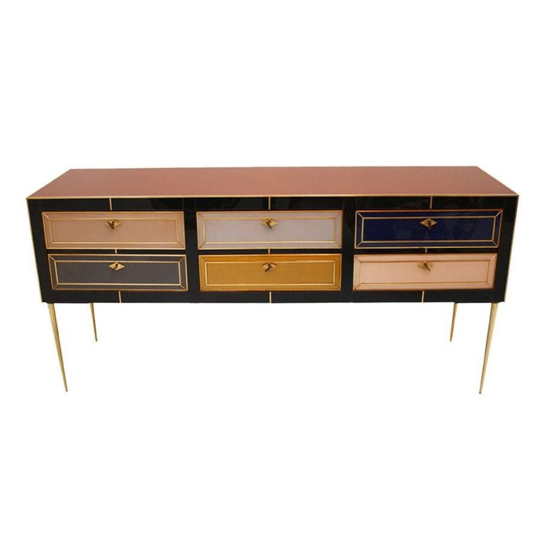 Italian sideboard composed by six drawers with wooden structure covered in colored glass and brass profiles, handles and feet.