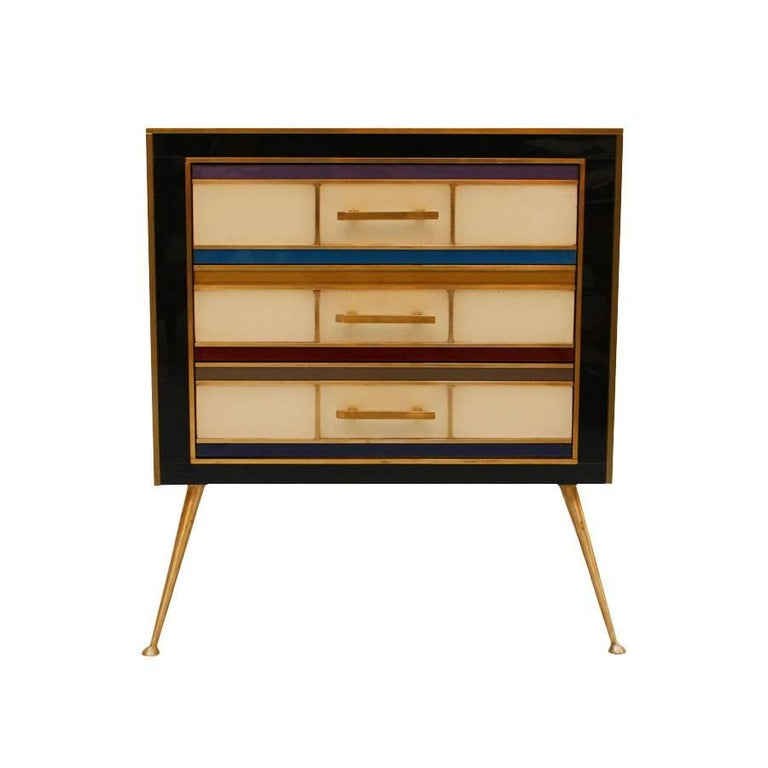 Pair of night stands with three drawers with structure in solid wood, covered in colored glass and brass details.