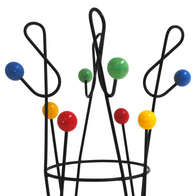 Mid-Century Modern coat rack designed by Roger Feraud. Composed of eight arms made of black lacquered iron structure, finishes in wood spheres in different colors. France, 1950s.