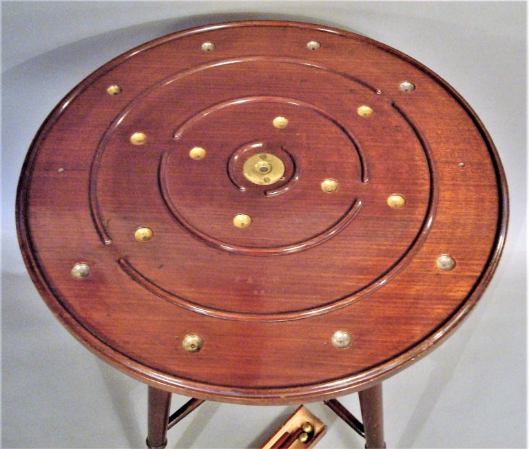 A rare late 19th century mahogany golf game table; this interesting table by Henry D Booth, stamped Parlour Golf Patent; the revolving circular top have a lane golf course with 16 brass holes and 2 opposing start positions. With a concealed drawer