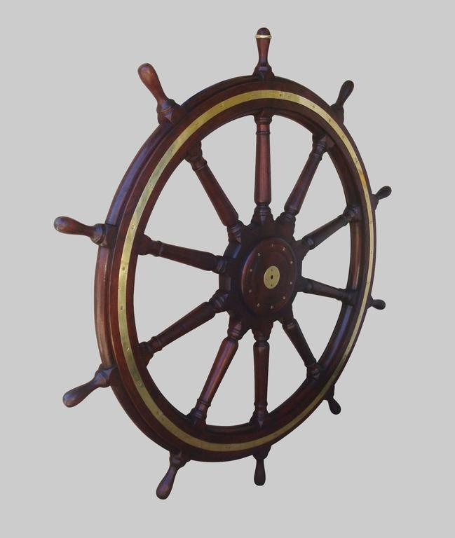 19th century very large teak ship's wheel; with ten turned spokes and ten shaped handles, one with original brass ring to indicate direction. The outer wheel with inset brass banding to both sides and the central hub with a later mahogany panel,
