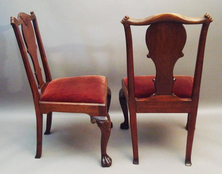 George II pair of Irish walnut side chairs, the shaped top rail with a central carved cresting and terminating in paper scroll ends above a wide, shaped solid splat; and a drop in seat housed in a shaped frame with a moulded edge; standing on