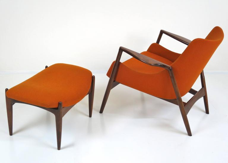 Rare Ib Kofod-Larsen lounge chair and ottoman. Solid wood frame has been refinished. The bright orange fabric is original. Imported by Selig. Measures: Chair 32