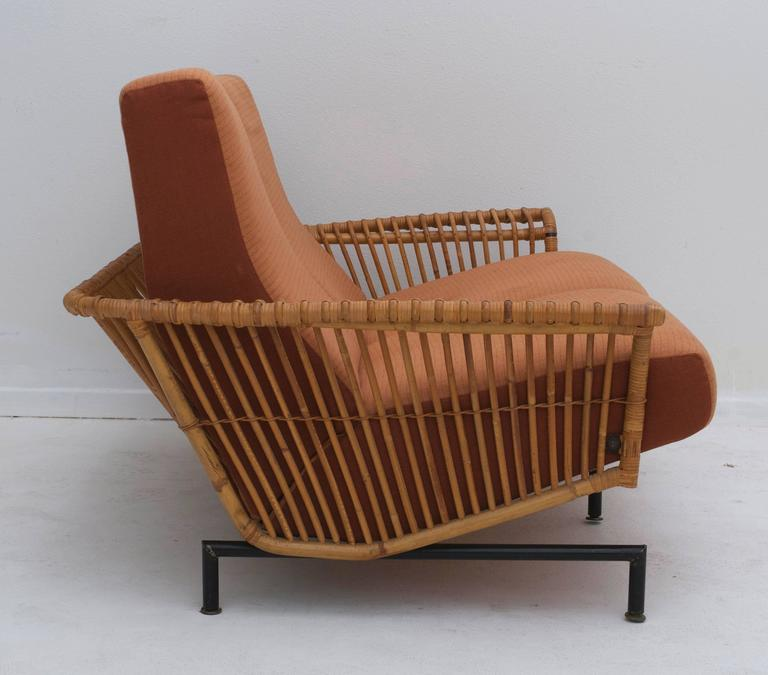 A sculptural Franco Albini style iron and caned settee. The back of the couch has its own internal support and the rattan floats around the back of it.  The curve of the arms create a sculptural shape that counterbalances the angular legs.