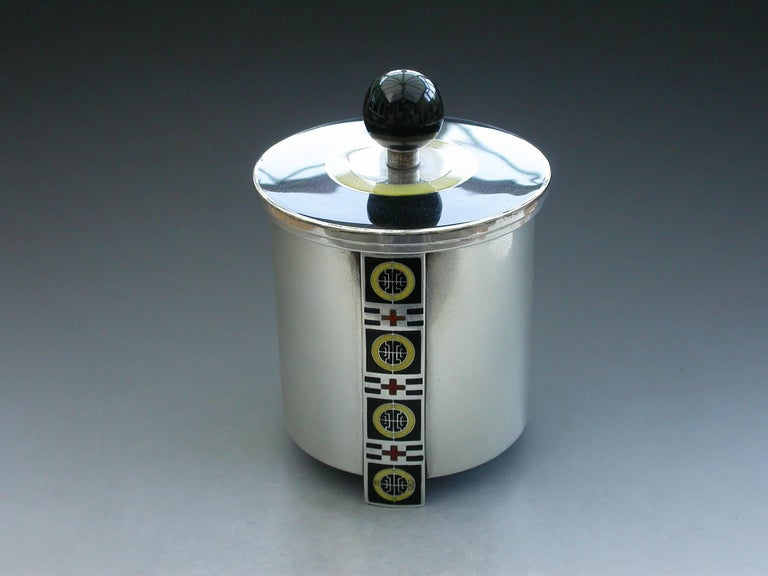 An unusual Norwegian Art Deco silver and enamel tea daddy of drum shape with three vertical supports enameled with geometric designs in black, red and yellow. The detachable cover in black enamel with a yellow band and ball finial.  By David