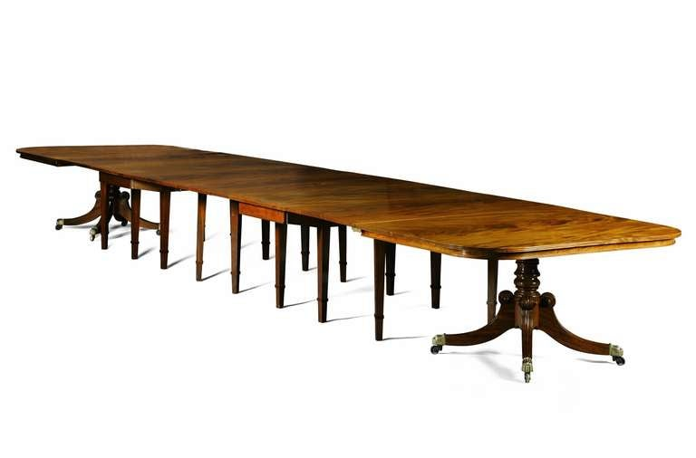 A Regency mahogany dining table from Durham Cathedral. This unusual and versatile Regency mahogany extending dining table is constructed in four sections and has a reeded edge to the rounded rectangular top. The tilt-top end sections are raised on
