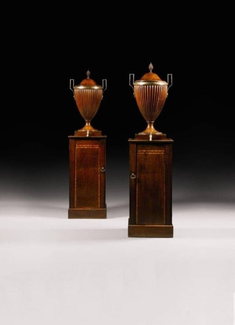 Each cistern is in the form of a fluted vase on a rectangular pedestal. The lead-lined vases have brass handles, removable lids with pineapple finials and taps. The crossbanded pedestals have cupboard doors enclosing slatted shelves for warming