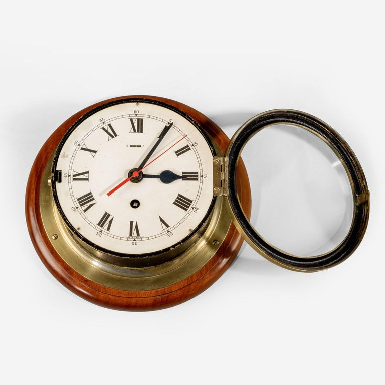 "6 ½"" dial Smith's Astral ship's bulkhead clock with brass bezel and black body on a mahogany back-board."
