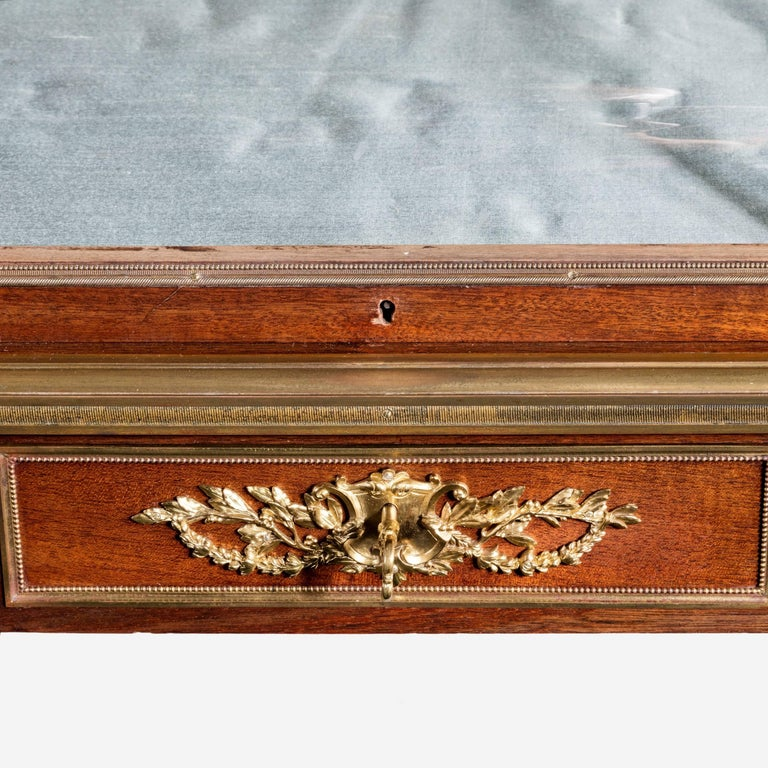 An attractive and unusual Napoleon III mahogany display table, the rectangular top surmounted by a shaped glazed panel which opens to allow access to the mirrored and silk lined interior, with three drawers disguised in the frieze, supported on