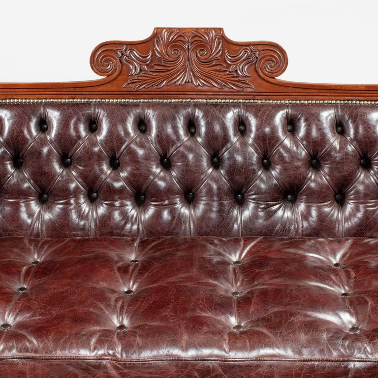 A late Regency mahogany sofa, boldly carved with roundels, the curved cresting centred on a scrolling motif and supported on lyre fronted legs with the original castors, re-upholstered in deep-buttoned burgundy leather.