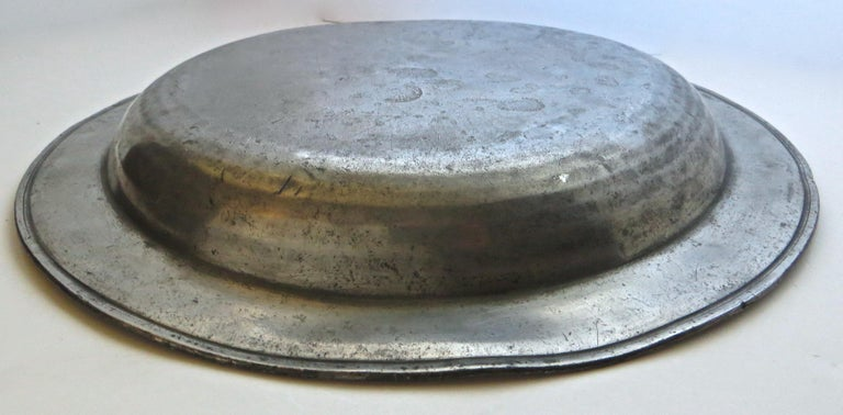 All original early 18th century pewter dish, hallmarked on the rear of the gently rounded bouge; three touchmarks are visible albeit not completely discernible. The most visible states