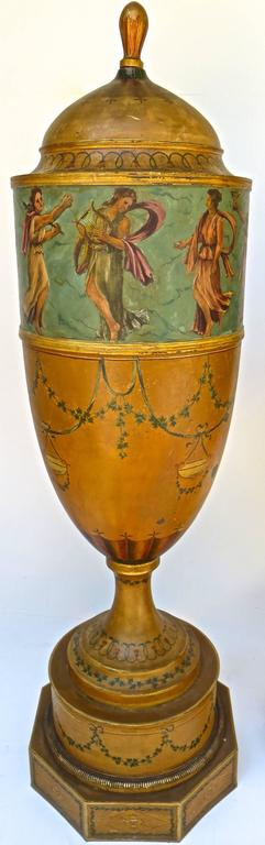 The copper domed covers are mounted with wood finials (possible added later). The shaped body of the urns terminate with turned socles which are in turn supported by drum like bases mounted by hexagonal plinths. The decoration is hand-painted in